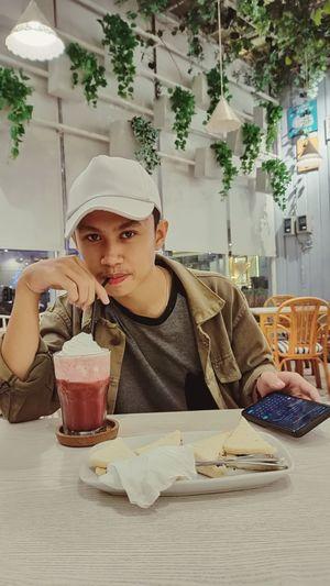 Portrait of teenager boy eating food at restaurant