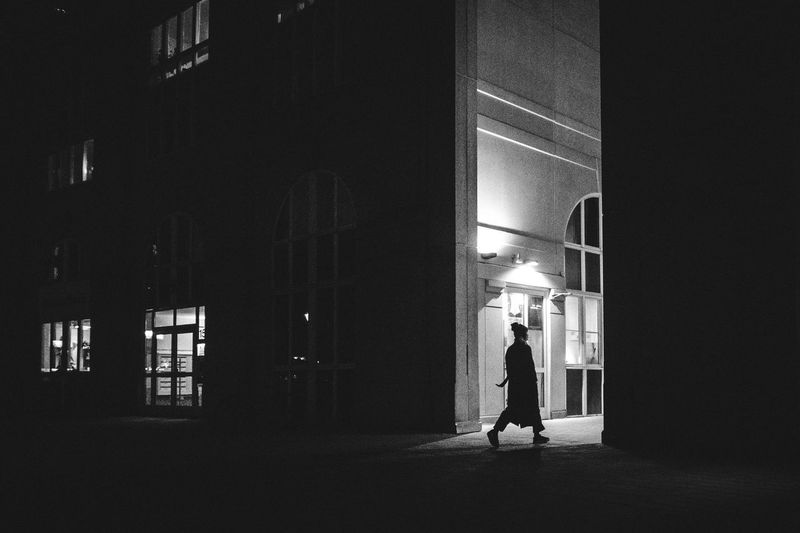Rear view of woman walking in illuminated building at night