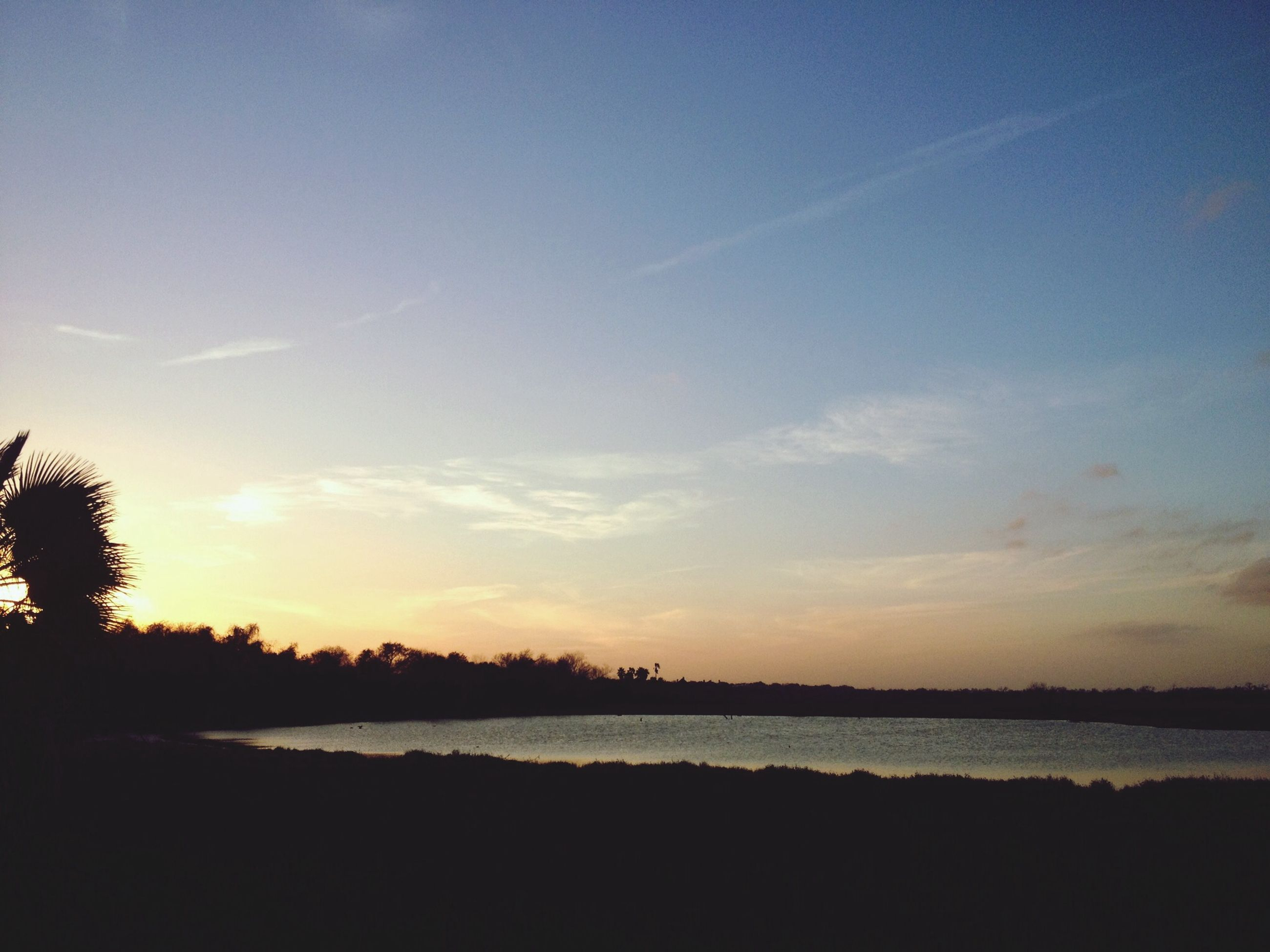 tranquil scene, tranquility, water, scenics, sunset, beauty in nature, silhouette, sky, tree, nature, idyllic, lake, sea, reflection, blue, calm, non-urban scene, outdoors, landscape, beach