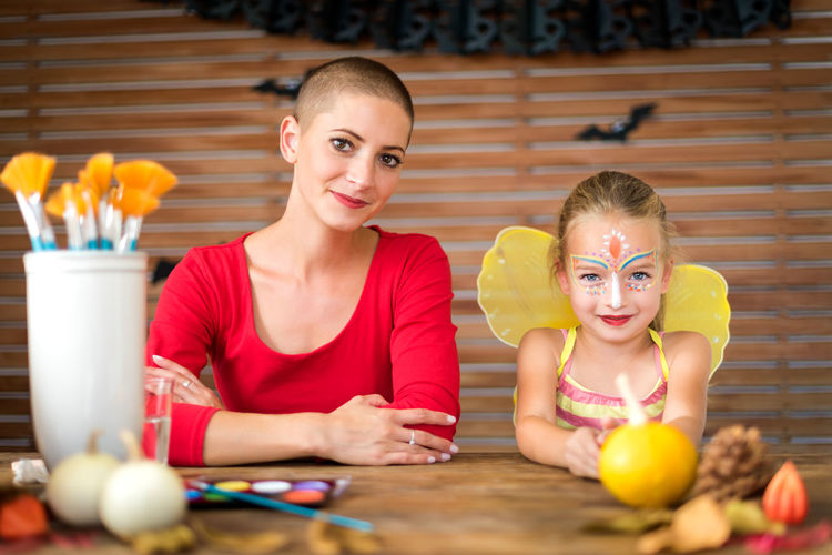 Portrait of smiling mother and daughter sitting at home