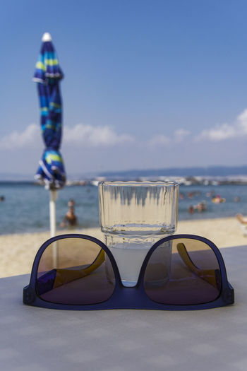 Sun glasses on restaurant table with alcoholic drink. Glass of ouzo on the rocks at Greek tavern in blurred beach background. Greek Taverna Summer In Greece Sun Glasses Beach Background Alcohol Alcoholic Drink Blue Sun Glasses Beach Greek Beach Greek Drink Greek Ouzo Greek Tavern Ouzo Ouzo Alcoholic Drink Ouzo Beach Greece Ouzo Glass Ouzo With Ice Scenics - Nature Sun And Alcohol Sun Glasses Alcohol Table Sun Glasses Ouzo Table Sun Protection Sunglasses Tavern  Tavern Tables Taverna Tsipouro