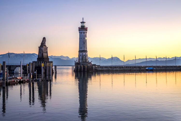 Lighthouse at commercial dock against sky during sunset
