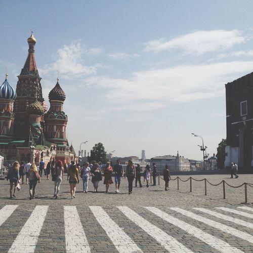 People walking in city against cloudy sky