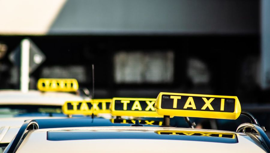Taxi text on car roofs in row