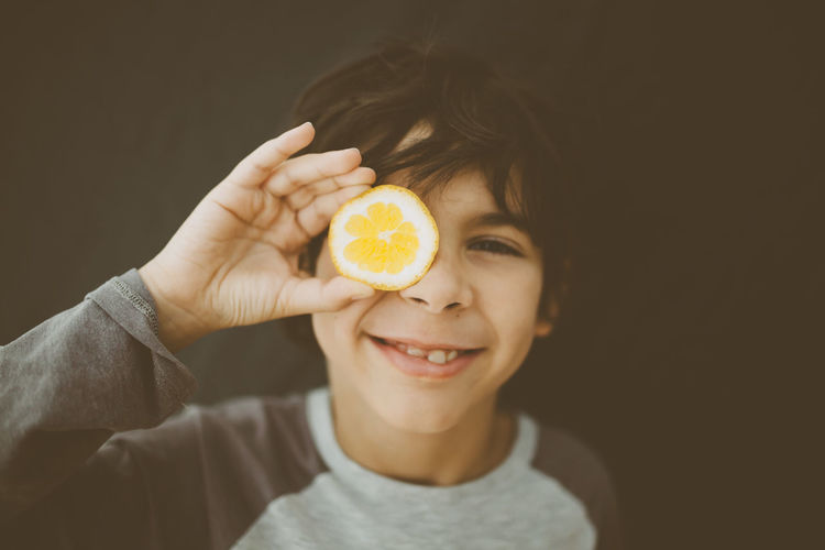 boy holding lemon Child Children Only Close-up Food Freshness Fruit Fun Happiness Healthy Eating Holding Indoors  Lemon One Boy Only Organic Food SLICE Uniqueness Vegan Yellow