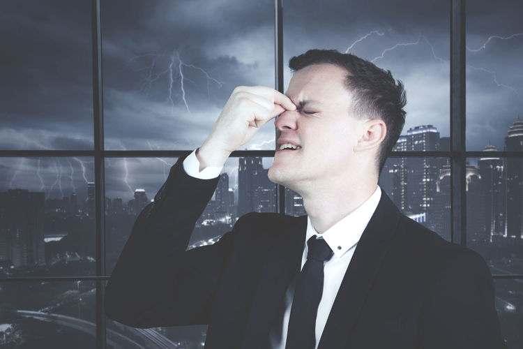 Stressed businessman standing in office against window