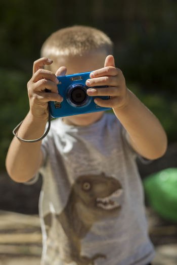 Child with camera [Cosina Cosinon 55mm f/1.2 MC] Activity Boys Camera - Photographic Equipment Child With Camera Day Digital Camera Focus On Foreground Front View Holding Leisure Activity Lifestyles Looking Through An Object Men Obscured Face One Person Outdoors Photographer Photographic Equipment Photographing Photography Themes Portrait Real People Technology Humanity Meets Technology
