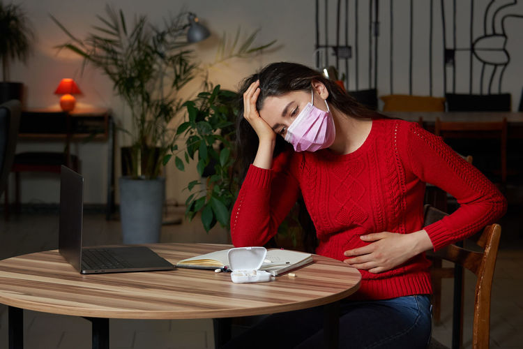 Sick woman sitting at home