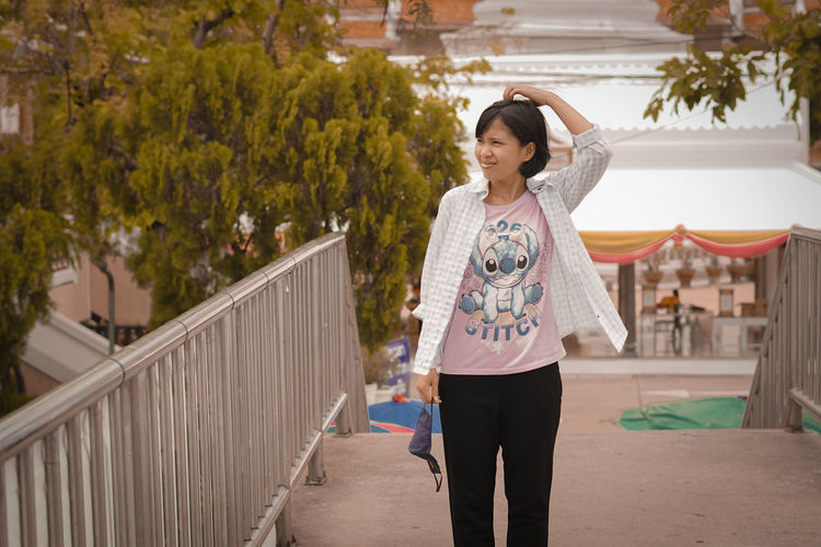 Full length of woman standing on railing against trees
