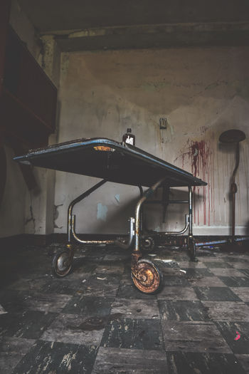 Abandoned shopping cart against wall in old building