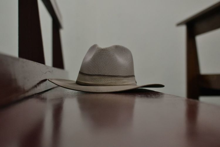 Close-up of hat on table against wall at home