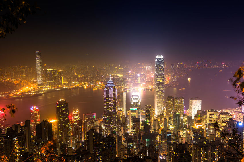 Spectacular aerial view of Victoria Harbor, skyscrapers and Hong Kong skyline at night. Skyline reflected in glass facade of a modern building. Hong Kong panorama skyline with Central Plaza, Hong Kong Convention and Exhibition Centre, Bank of China, HSBC, Two International Finance Centre, Observation Wheel. HongKong Hong Kong City Hong Kong Sunset Skyline Night Cityscape Business Aerial View Light Show Laser Show Skyscraper Victoria Harbor Panorama City Building Exterior Architecture Built Structure Building Illuminated Office Building Exterior Crowd Sky Landscape Urban Skyline City Life Modern Tall - High Residential District Nature Outdoors Financial District