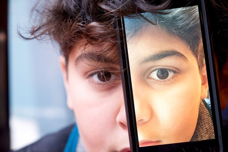 Close-up portrait of teenage boy with mobile phone