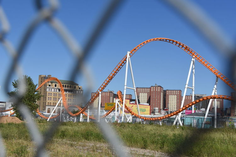 Rollercoaster Seen Through Chainlink Fence Against Blue Sky