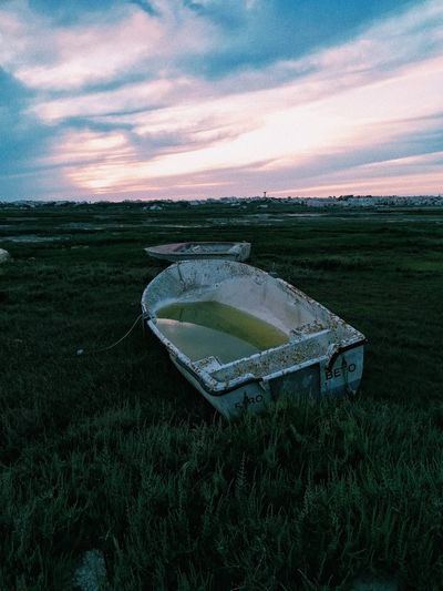 Abandoned car on field against sky during sunset