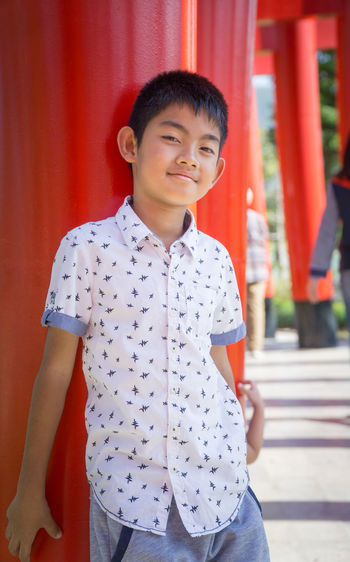 Portrait of smiling boy standing against red torii