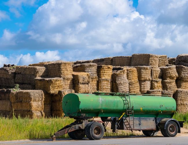 Abandoned fuel tanker by hay bales on road