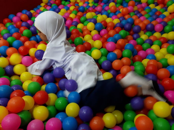 High angle view of girl playing on colorful balls