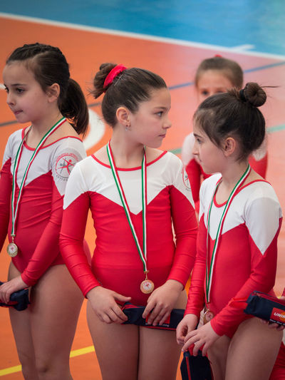 Verona, Italy - March 17, 2019: Award ceremony at the end of a junior women's artistic gymnastics competition. Athlete AWARD Caucasian Celebration Ceremony Challenge Champion Child Children Sports Competition Congratulations Cup Excellence Fitness Girl Gold Golden Gymnast  Gymnastic Gymnastics Happy Kid Medal Physical Education Presentation Ceremony Presenting Reward Satisfaction School Children Smile Sport Sport Competition Sportive Sporty Successful Victory Win Winner Young