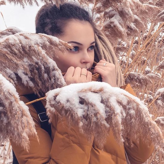 Thoughtful young woman standing amidst frozen plants during winter