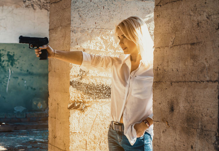 Woman holding gun while standing amidst columns