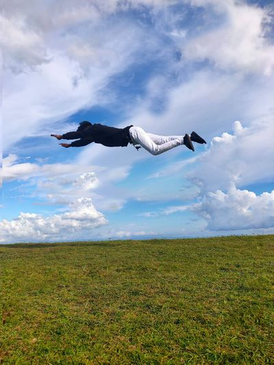 Young man levitating over land against sky