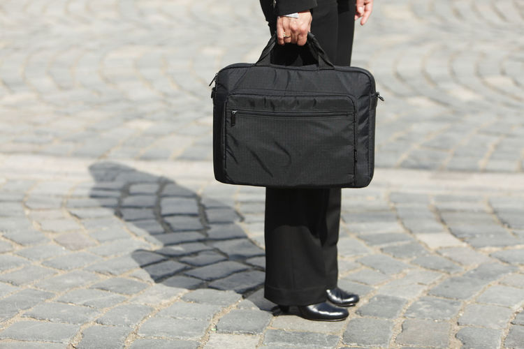 Low section of businesswoman holding bag while standing on city street