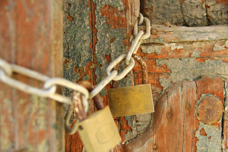 Close-Up Of Padlocks With Metal Chain On Weathered Door