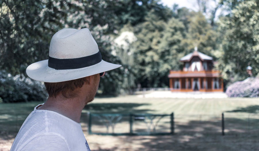 Rear view of man wearing hat against trees