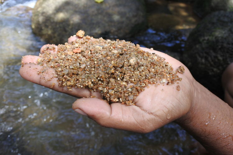 Cropped hand of man holding wet gravel