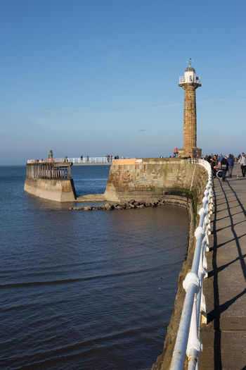The old lighthouse on the West pier at Whitby, North Yorkshire on a clear, sunny day. Water Architecture Sky Built Structure Building Exterior Sea Tower Clear Sky Guidance Lighthouse Nature Travel Security Safety Day Protection Direction Building Tourism Outdoors Copy Space Whitby Harbour Pier Blue Sky Fence