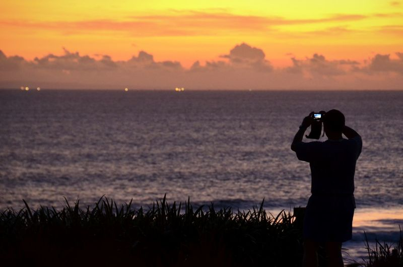 Rear view of man photographing scenic view of sunset and sea