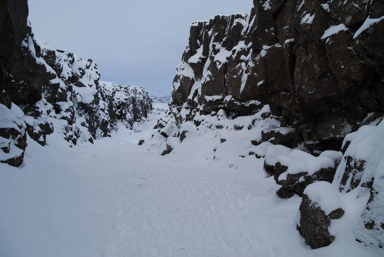 Snow on rock against sky