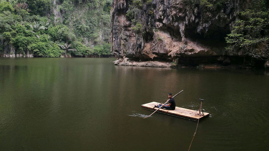 Man on wooden raft in lake
