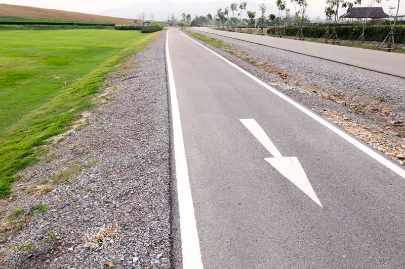 Asphalt Day Diminishing Perspective Direction Dividing Line Environment Field Grass Land Marking Nature No People Outdoors Plant Road Road Marking Sign Symbol The Way Forward Transportation vanishing point