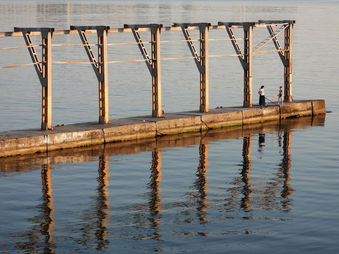 Reflection of man on wooden pier over sea