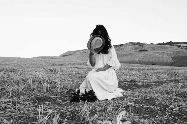 Woman covering face with hat on land against clear sky