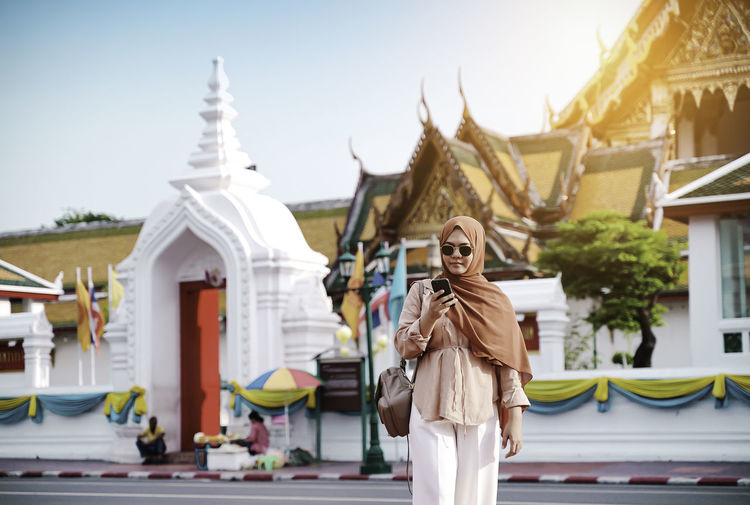 Woman standing outside temple against building