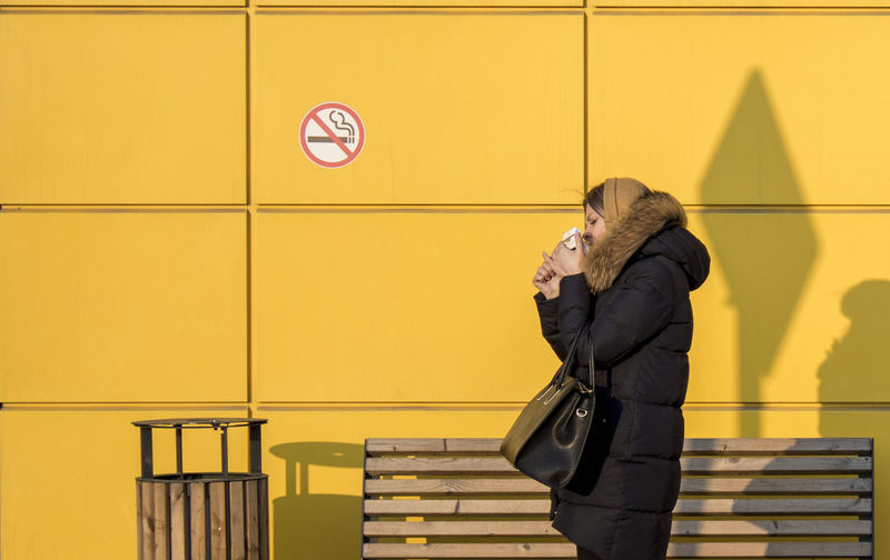Side View Of Young Woman Smoking Against No Smoking Sign On Wall