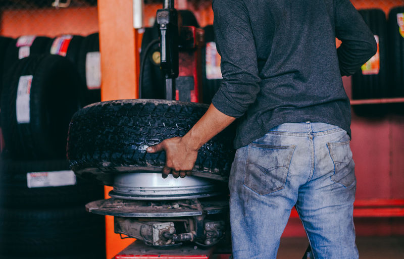 Rear view of mechanic working in workshop