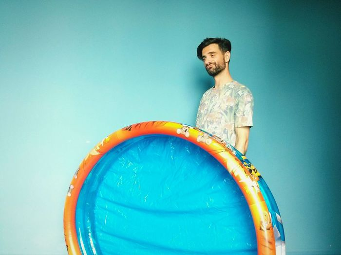 Confused Young Man Holding Wading Pool Against Blue Background