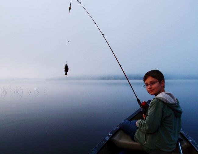 Boy fishing in lake against sky