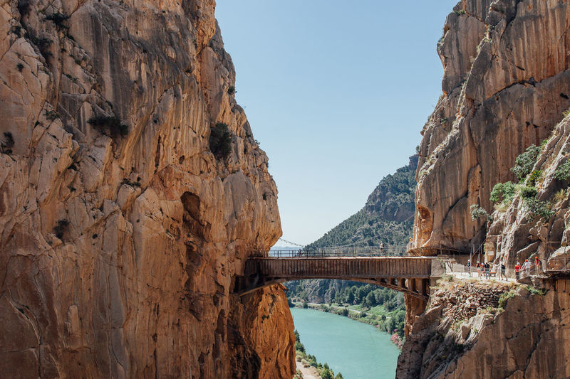 Footbridge over mountain against clear sky