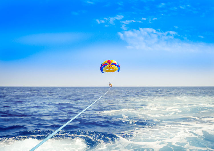 Parachute flying over sea against blue sky