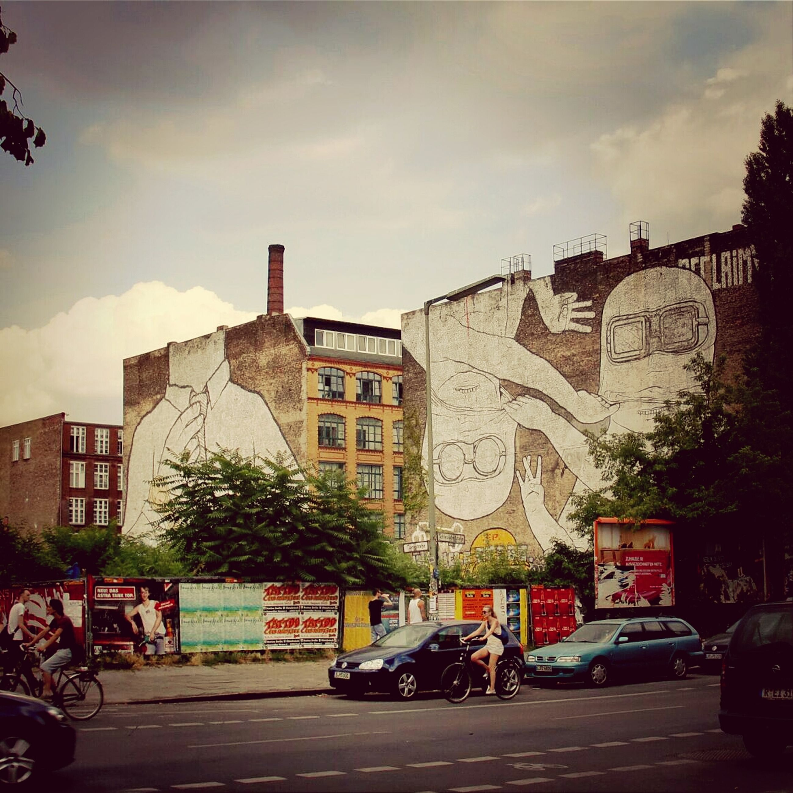 architecture, building exterior, built structure, sky, text, street, tree, cloud - sky, city, graffiti, outdoors, day, road, western script, incidental people, cloud, art, transportation, art and craft, communication