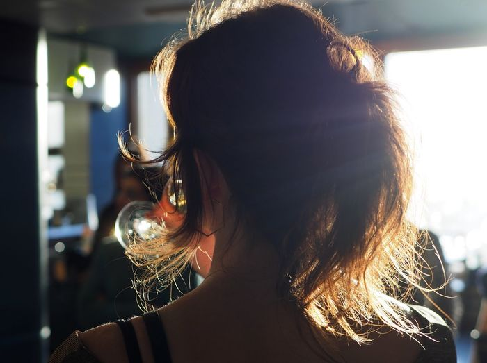 Headshot Hairstyle One Person Hair Long Hair Portrait Real People Focus On Foreground Adult Leisure Activity Lifestyles Women Rear View Young Adult Indoors  Young Women Brown Hair Illuminated Sunlight Human Hair Drinking Champagne