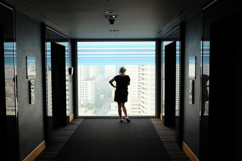 Rear View Of Woman Looking Through Glass Window In Hotel Corridor