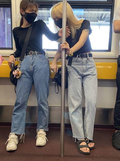 Full length of women wearing mask standing in train