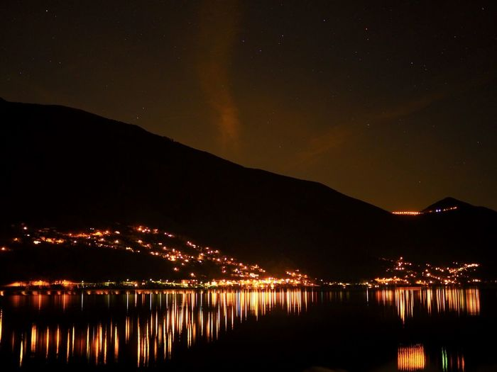 Astronomy Beauty In Nature Illuminated Mountain Nature Night No People Outdoors Reflection Scenics Sky Star - Space Water Waterfront