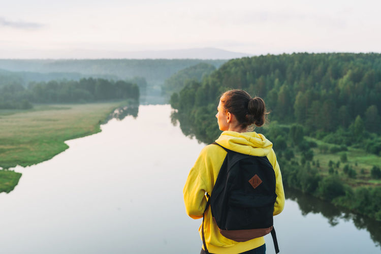 Young woman girl traveler in yellow hoodie with backpack looking at sunrise on beautiful view. local